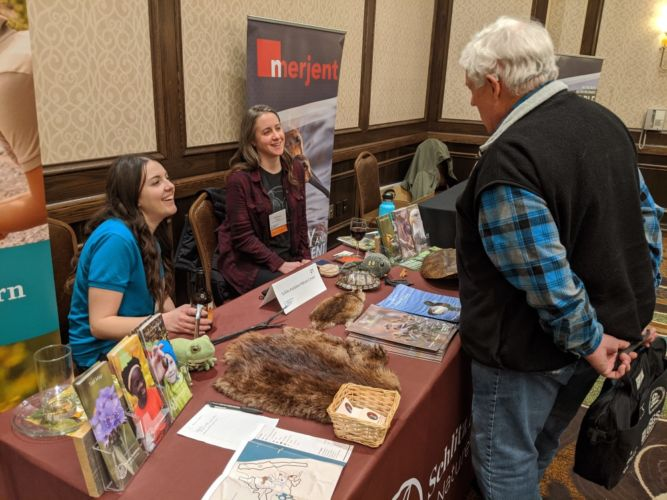 a conference attendee speaks with exhibitors